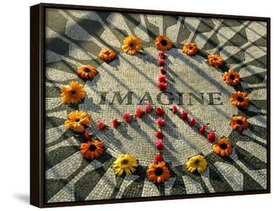 A Makeshift Peace Sign of Flowers Lies on Top John Lennon's Strawberry Fields Memorial