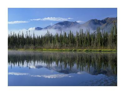 Lake reflecting mountain range and forest, Kluane National Park, Yukon, Canada