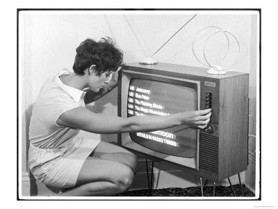 Woman Adjusts Her TV Set Which is Showing a List of the Afternoon's Programs