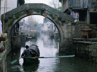 A Bamboo Boat Makes Its Way Through Shaoxing Water Town, Shaoxing, Zhejiang, China