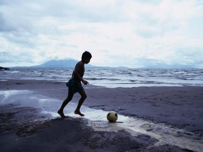 Boy Kicking Soccer Ball on Beach, Lake Nicaragua, Granada, Nicaragua