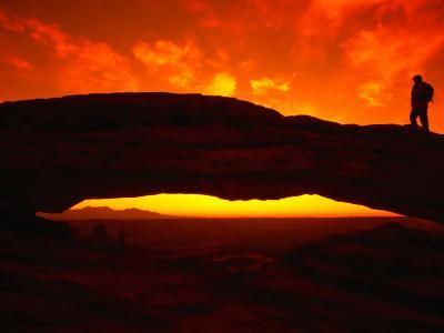 Silhouette of a Hiker on Mesa Arch Against a Spectacular Orange Sky, Utah, USA
