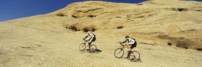 Two Men Mountain Bilking on Rocks, Slickrock Trail, Moab, Utah, USA