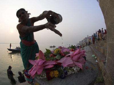 Woman Pouring Water Over Flowers on an Altar as a Religious Ritual, Varanasi, India