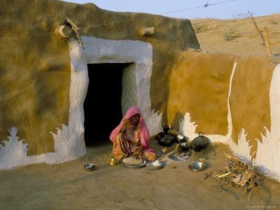 Woman Cooking Outside House with Painted Walls, Village Near Jaisalmer, Rajasthan State, India