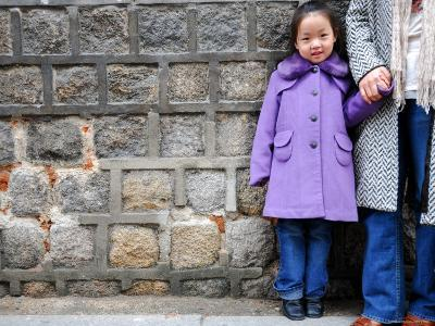 Young Girl Standing Against Stone Wall, Seoul, South Korea