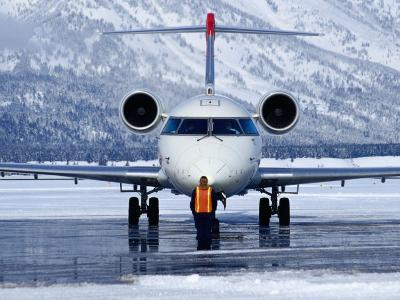 Aircraft at Jackson Hole Airport Surrounded by Snow-Covered Fields and Hills, Jackson Hole, Wyoming