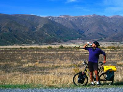 Cyclist Having a Drink on the Side of the Highway between Twizel and Omarama, Otago, New Zealand