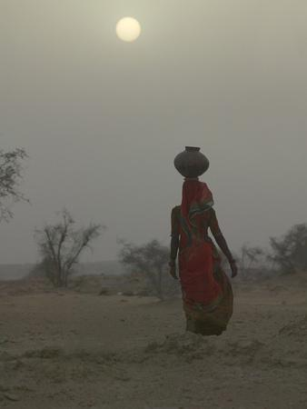 Woman Carrying Water Jar in Sand Storm, Thar Desert, Rajasthan, India