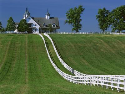 Double White Fence Flows from an Elegant Horse Barn, Woodford County, Kentucky, USA