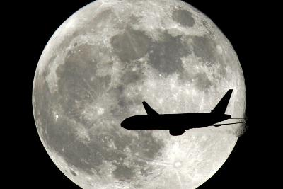A Jet Plane Passes in Front of the Full Moon Above Surfside, Fla.