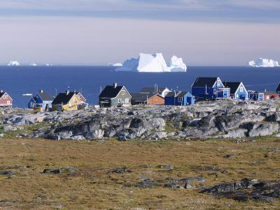 Painted Village Houses in Front of Icebergs in Disko Bay, West Coast, Greenland