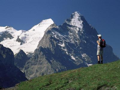 Hiker Looking to the Snow-Covered Monch and the North Face of the Eiger, Swiss Alps, Switzerland