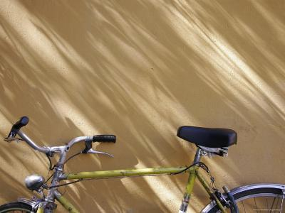 Bicycle Leaning against a Shadowed Yellow Wall, Parma, Italy
