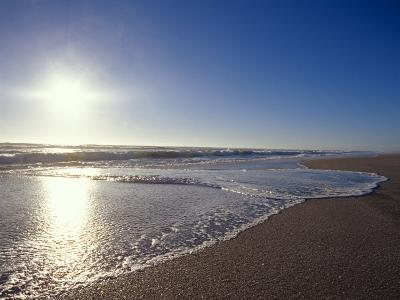 Gentle Waves Lap Onto a Pristine Sandy Beach with the Sun Reflecting, Australia