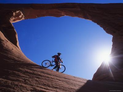 Mountain Biker Stands under an Arch