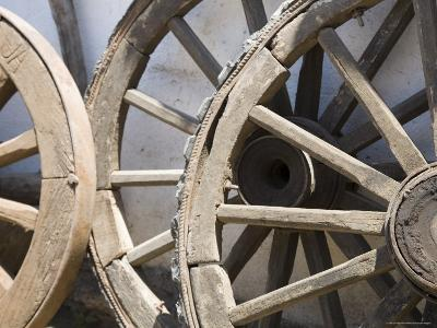 Old Wooden Wagon Wheels Leab against a Whitewashed Wall