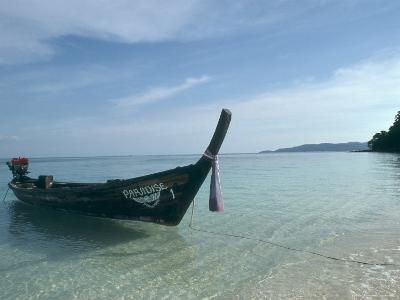 Wooden Boat Named Paradise is Tethered to a Palm Tree