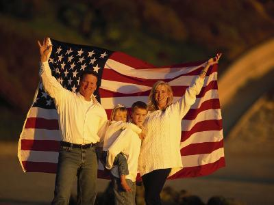 Family Holding Up the American Flag