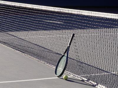 Tennis Racquet Against Net with Ball