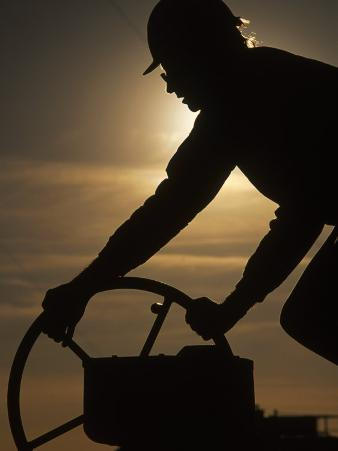 Silhouette of Oil and Gas Worker Turning Valve