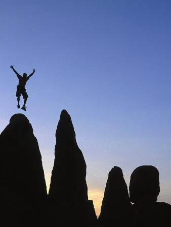 Silhouette of Man Jumping on Top of Rock