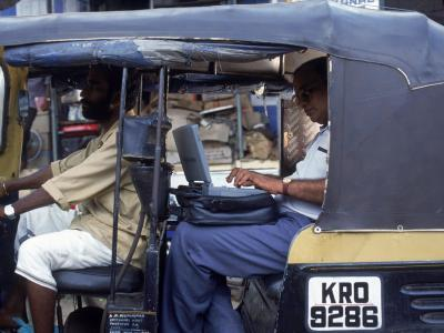 Man Uses Laptop in Back Seat of Rickshaw, India