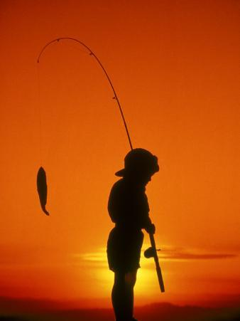 Silhouette of Boy Fishing at Sunset