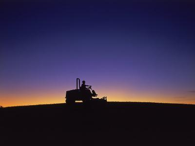Silhouette of Worker Cutting Grass at Sunrise