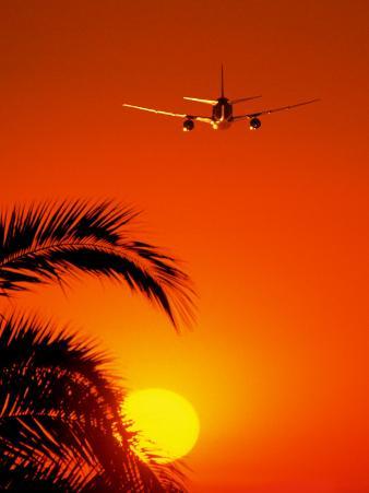 Airplane Flying Over Sunrise