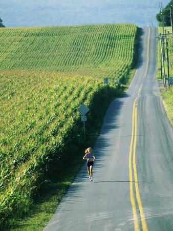 A Woman Jogs Down a Country Road Alongside a Field of Corn