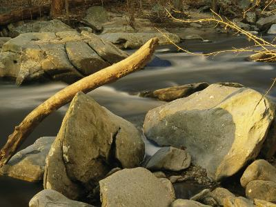 Rock Creek Rushes Past Large Boulders and Driftwood at Sunset