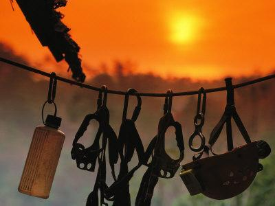 Caving Equipment and Bottle Hang on Line against a Fiery Sun and Sky