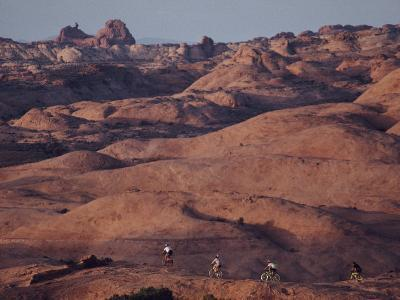 Mountain Bike Riders on Slickrock Trail Near Moab, Utah; Arches National Park is in the Background