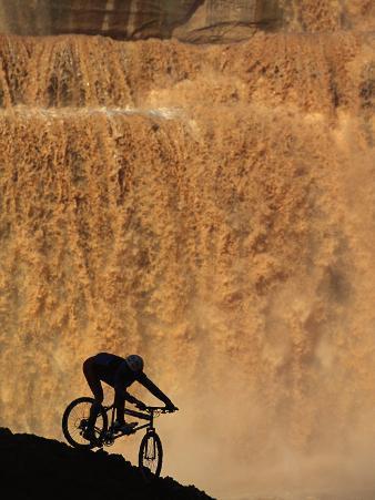 Mountain Biker Pedals Past Rushing Winter Snow Melt at Grand Falls