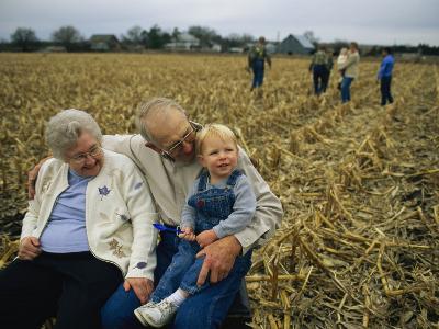 Smiling Grandparents Hold Their Grandson