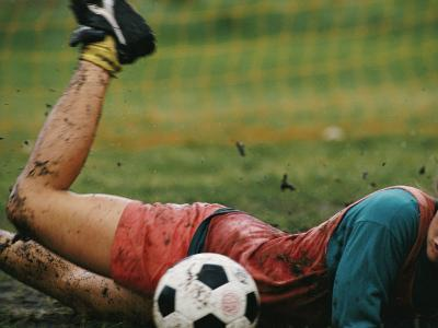 A Soccer Player Lands in the Mud in an Attempt to Field the Ball