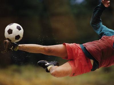 A Man Bends Sideways as He Kicks a Soccerball