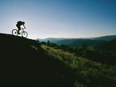 A Bicyclist Rides Along the Ridge of a Mountain