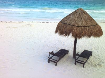 A Palm Frond Umbrella and Two Chairs on a White Sand Beach
