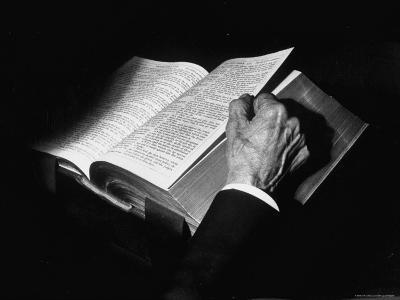 Dramatic Close Up of Man's Hand Turning the Leaves of Large Bible