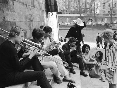 Young Parisian Musicians Enjoying an Impromptu Outdoor Concert on the Banks of the Seine River