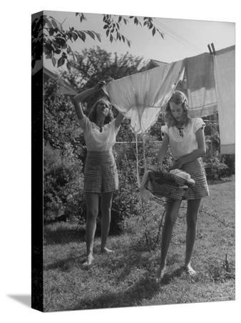 Teenage Twin Girls Hanging Laundry on Clothesline