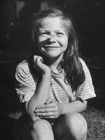 Young Girl with Long Hair and Raggedy Shirt, Smiling, Wearing Seed Pod on Nose