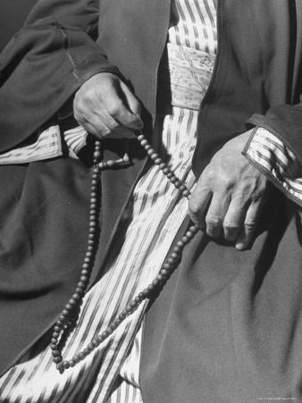 Moslem Sheikh Holding Amber Beads
