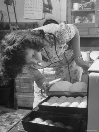 Woman Baking Loaves of Bread and Biscuits