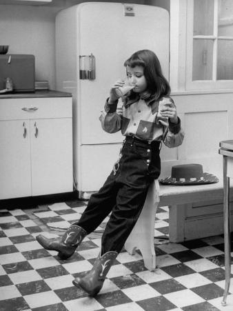 Young Girl Wearing Cowgirl Outfit Drinking Milk and Eating Sandwich in Kitchen