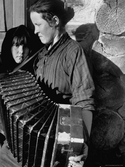 Woman Playing a Russian Button Accordion as Her Young Girl Looks On