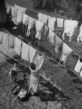 Mother Hanging Laundry Outdoors During Washday
