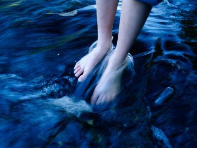 A Close View of Feet in River Water